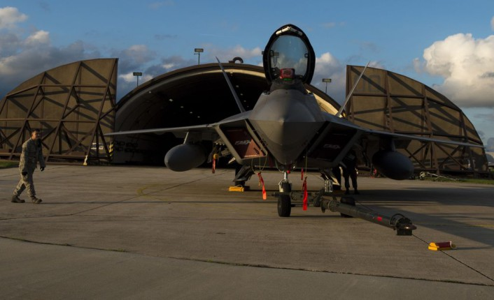 A member of the 95th Fighter Squadron at Tyndall Air Force Base, Fla., observes an F-22 Raptor fighter aircraft at Spangdahlem Air Base, Germany, Aug. 28, 2015. The U.S. Air Force deployed four F-22 Raptors, one C-17 Globemaster III and more than 50 Airmen to Spangdahlem in support of the first F-22 European training deployment. The inaugural F-22 training deployment to Europe is funded by the European Reassurance Initiative, a $1 billion pledge announced by President Obama in March 2014. (U.S. Air Force photo by Airman 1st Class Luke Kitterman/Released)