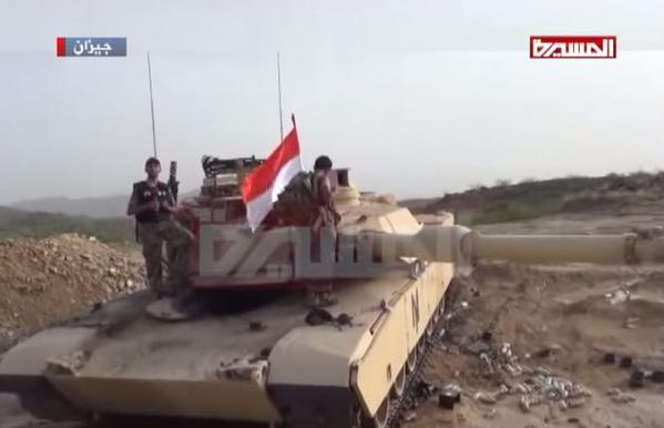 An Al Masirah reporter and Houthis stand next to a captured Saudi M1 Abrams tank 2