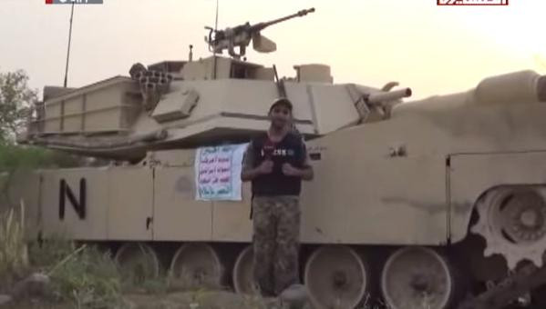 An Al Masirah reporter and Houthis stand next to a captured Saudi M1 Abrams tank 3