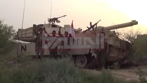 An Al Masirah reporter and Houthis stand next to a captured Saudi M1 Abrams tank 4